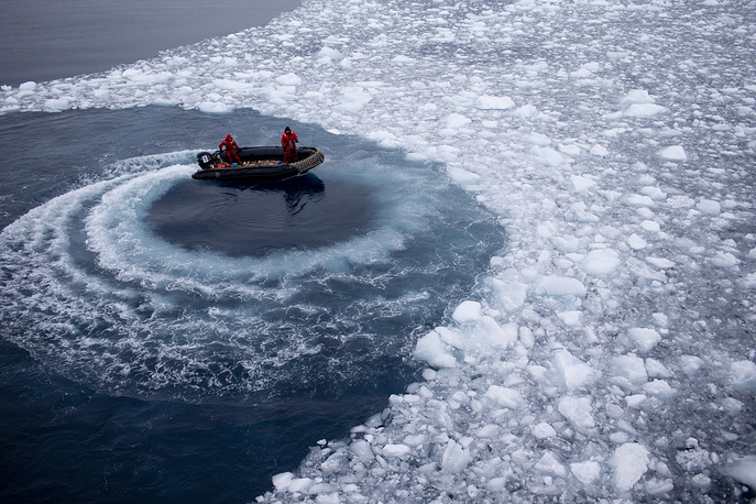Chilean Navy officers pushing away ice by moving their boat in circles in Antarctica