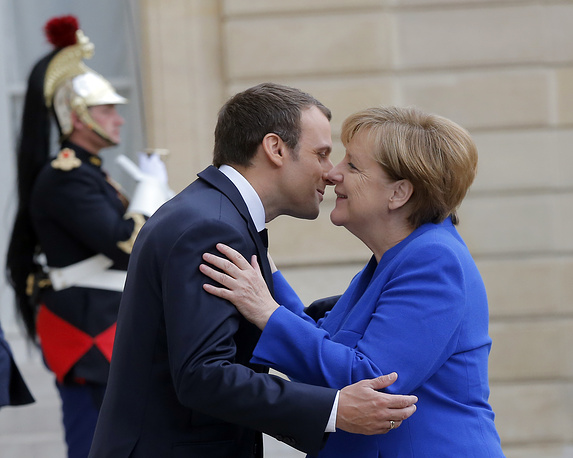 French President Emmanuel Macron greets German Chancellor Angela Merkel prior to a joint Franco-German cabinet meeting at the Elysee Palace in Paris, July 12
