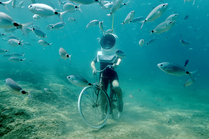 A woman dives and pretends to ride a bike in Underwater Park in Pula, Croatia, August 1