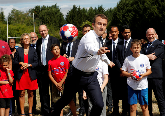 French President Emmanuel Macron kicks the ball as he visits the recreational centre for children in Moisson, France, August 3
