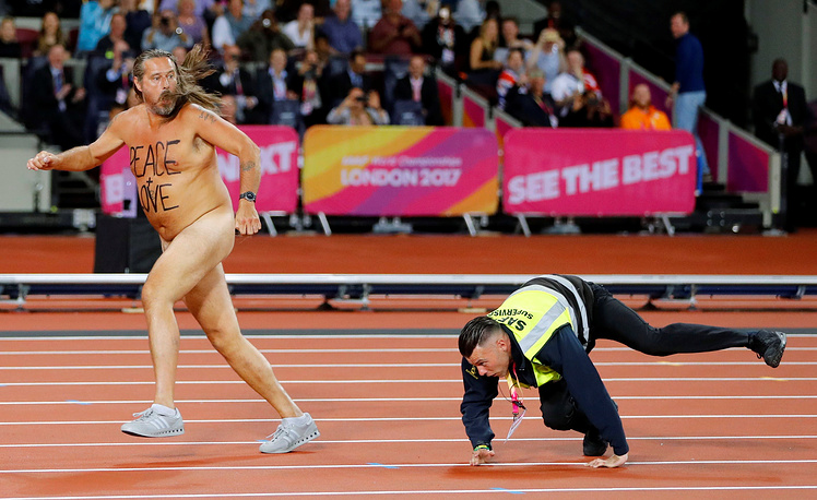 A streaker is chased by a steward after invading the track in London Stadium, Britain, August 5
