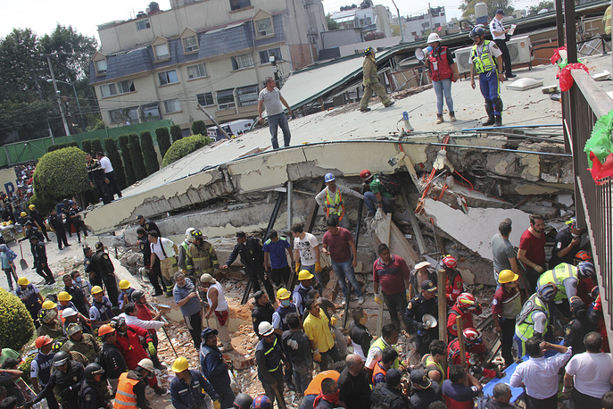 Rescue workers search for children trapped inside the collapsed Enrique Rebsamen school in Mexico City