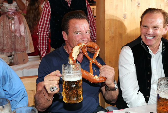Arnold Schwarzenegger eats a pretzel during the Oktoberfest at Schuetzen Festzelt at Theresienwiese in Munich, Germany, September 26