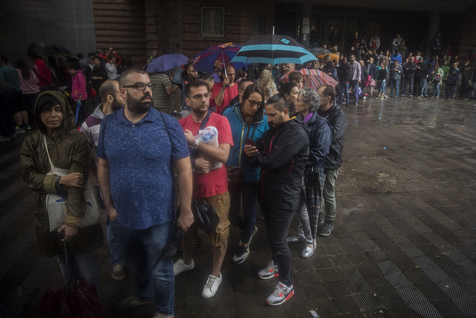 People queue to vote at a school listed to be a polling station by the Catalan government in Barcelona, Spain