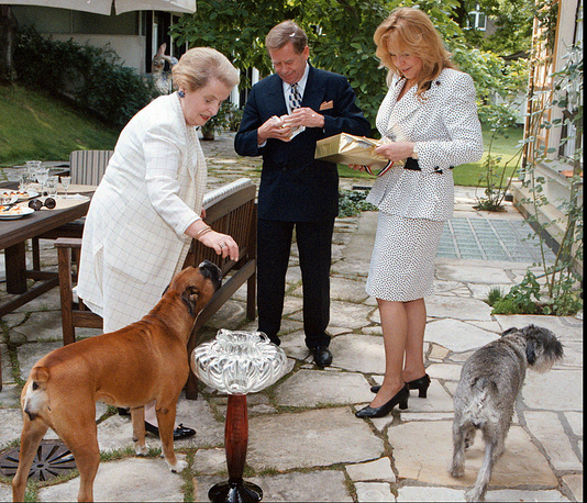 US Secretary of State Madeleine Albright plays with Sugar, one of Czech President Vaclav Havels' two dogs, as his wife Dagmar open the boxes with presents during their meeting in Havel's private residence in Prague, 1997