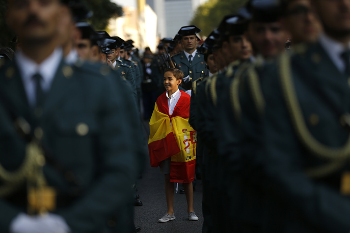"A young boy, draped in the Spanish flag, stands amongst Spanish military personnel as they prepare for a military parade during the national holiday known as ""Dia de la Hispanidad"" or Hispanic Day, in Madrid, Spain, October 12"