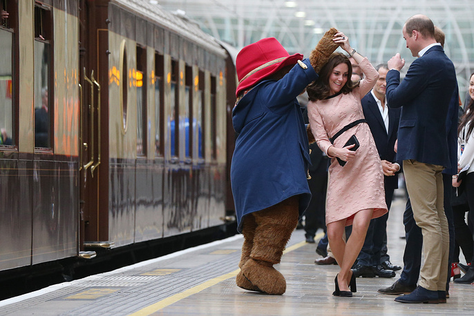 Catherine, Duchess of Cambridge dances with Paddington bear on platform 1 at Paddington Station as she meets the cast and crew from the forthcoming film Paddington 2, London, UK, October 16