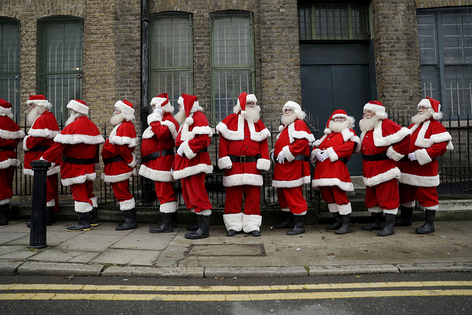 Performers dressed as Santa Claus stand posed in a line during a photocall for the media for the Ministry of Fun Santa School outside the Ragged School Museum in east London, November 16