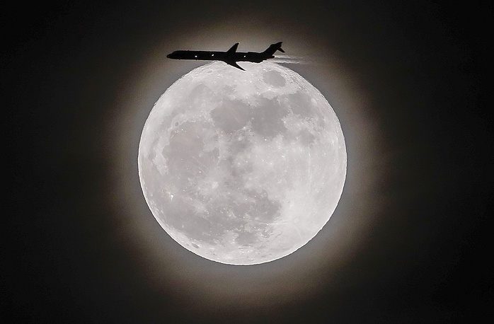 An airplane crosses in front of the moon in Avondale Estates, USA