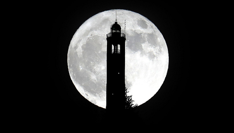 Supermoon rises above the lighthouse of San Maurizio in Brunate, near Como, Italy