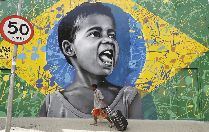 A man walks past a wall mural depicting a child superimposed on a representation of the Brazilian national flag, in Sao Paulo, Brazil, December 5