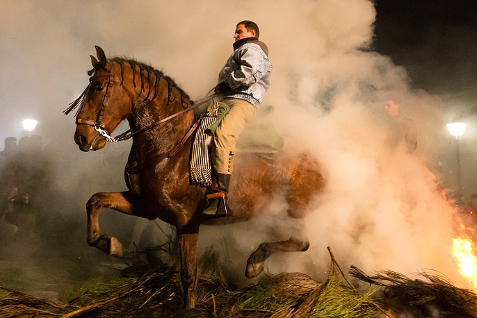 A horse and rider jump over the fire asking Saint Anthony for protection against diseases