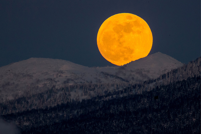 The red full moon rises over hills near the city of Yuzhno-Sakhalinsk on Sakhalin Island in Russia's Far East