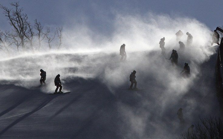 Course crew are shrouded in snow as they carry ski gates after the women's giant slalom was postponed due to high winds at the 2018 Winter Olympics at the Yongpyong Alpine Center, Pyeongchang, South Korea, February 12
