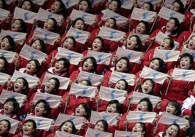 North Korean supporters hold up Korean unification flags during the ladies' 500 meters short-track speedskating in the Gangneung Ice Arena