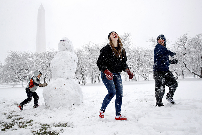 A boy works on a snowman as his siblings laugh while having a snowball fight during the spring snowfall in Washington, USA, March 21