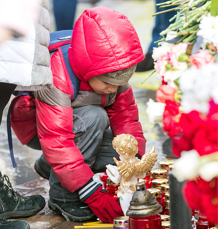 A child with a candle outside the shopping centre in Kemerovo where at least 64 were killed in a fire