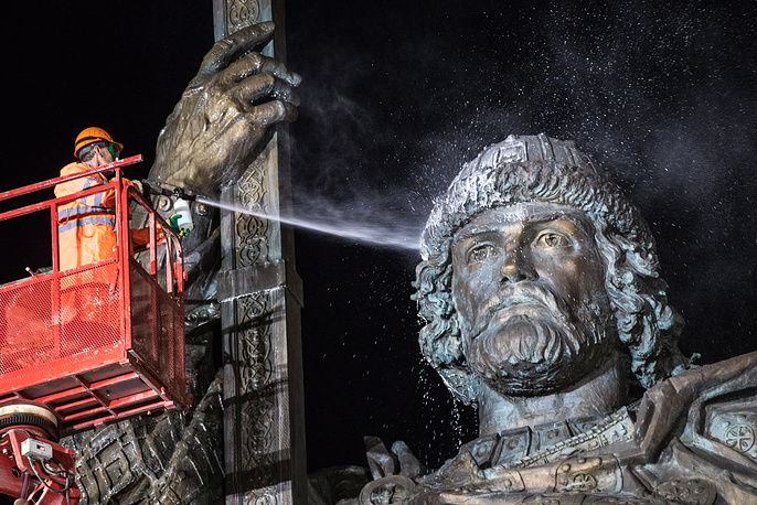 Public utility workers wash a monument to Prince Vladimir the Great, a ruler who Christianized the Kievan Rus', on Borovitskaya Square, Moscow, April 19