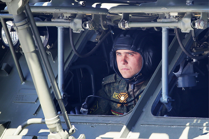 A serviceman inside a military vehicle during a Victory Day military parade