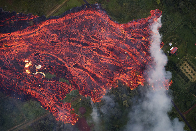 A massive fast moving lava flow consumes everything in its path, as the flames from the remnants of one home burns on the left, while it approaches another on the right. Pahoa, Hawaii, USA