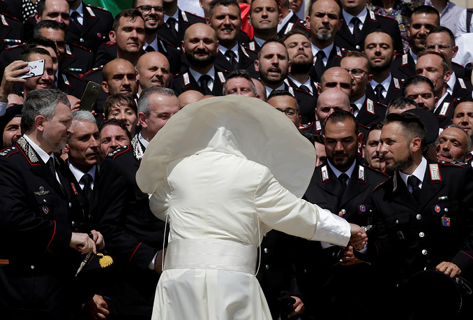 A gust of wind blows the Pope's mantel as he greets the Carabinieri after the Wednesday general audience in Saint Peter's square at the Vatican, May 30