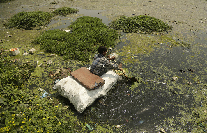A young boy collects plastic and other recyclable material from the polluted waters of Babdemb lake in Srinagar, Indian controlled Kashmir