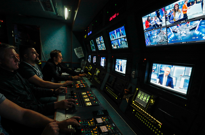 NTV Channel employees seen in an outside broadcast van during Vladimir Putin's Q&A session