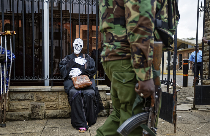 An armed police officer walks past an environmental protester wearing a skeleton costume as she demonstrates outside parliament against recent government plans to mine coal and open a coal-fired power plant, in downtown Nairobi, June 5