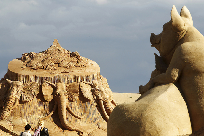 Visitors look at a sand sculpture at the 12th International Sands Sculpture Festival in Jelgava, June 19