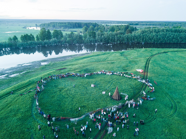 A round dance in a field during a summer solstice celebration