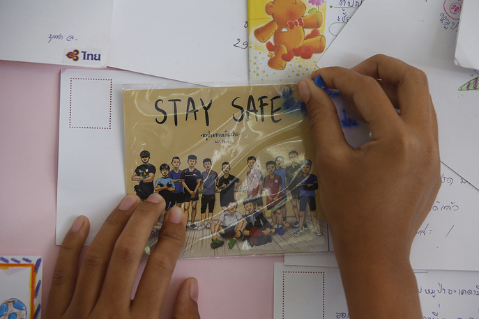 A Thai well wisher puts a poster to pray for boys and their coach in Mae Sai, northern Thailand