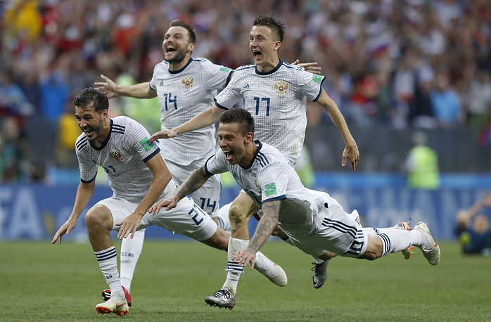 Russia's Fyodor Smolov dives as he celebrates with teammates after Russia defeated Spain in a penalty shoot out during the round of 16 match between Spain and Russia at the Luzhniki Stadium in Moscow, July 1