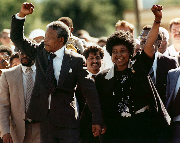 Nelson Mandela and wife Winnie, walking hand in hand, raise clenched fists upon his release from Victor prison, Cape Town, 1990.