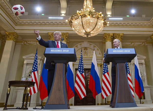 US President Donald Trump tosses a ball to his wife First Lady Melania Trump after Russian President Vladimir Putin presented it to him as a gift during a news conference after their meeting at the Presidential Palace in Helsinki, July 16