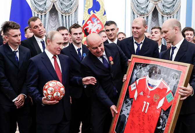Russia's President Vladimir Putin receives a ball and a Number 11 football jersey from the head coach of Russian's national team Stanislav Cherchesov and Russian football players after a ceremony to award national decorations to Russia's national men's football team and coaches at the Kremlin, Moscow, July 28
