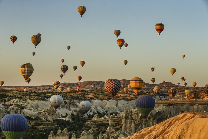 Hot air balloons, carrying tourists, rise into the sky at sunrise in Cappadocia, August 7