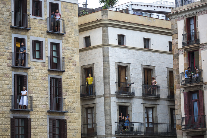 People on their balconies watch as participants make human towers in Barcelona