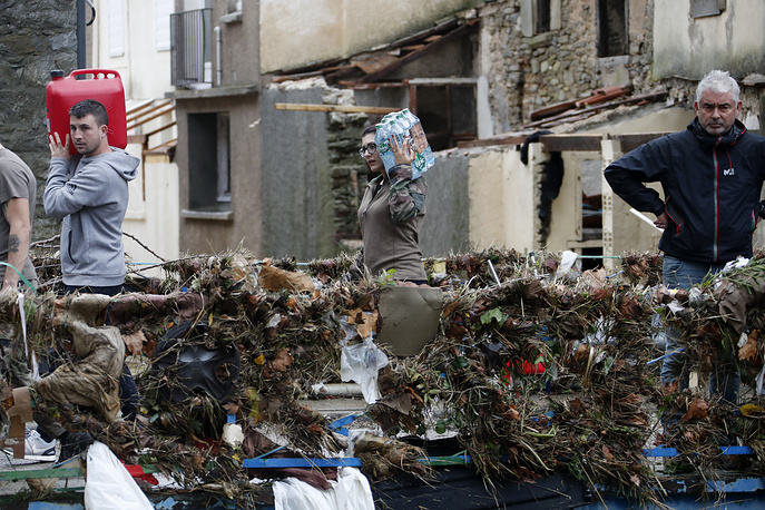 People carry water through damages in Villegailhenc, France