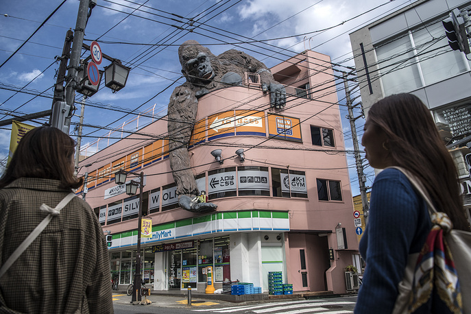 A large King Kong sculpture hangs over the side of a building in Tokyo, October 24