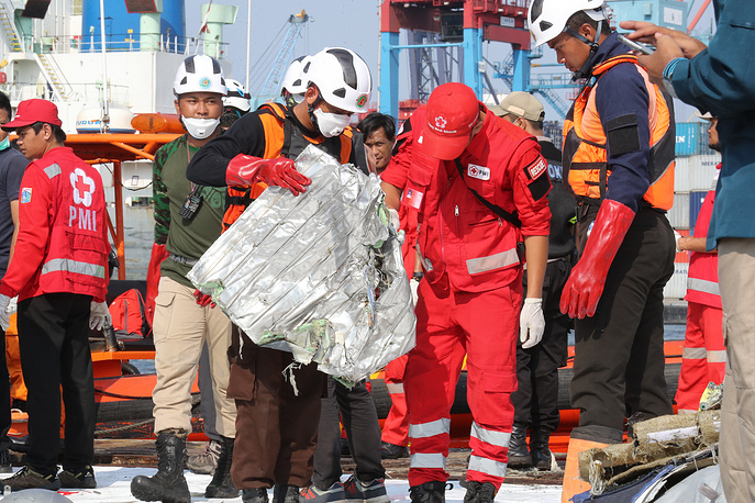Indonesian rescue team members collecting the remains of the crashed plane at Tanjung Priok Harbour