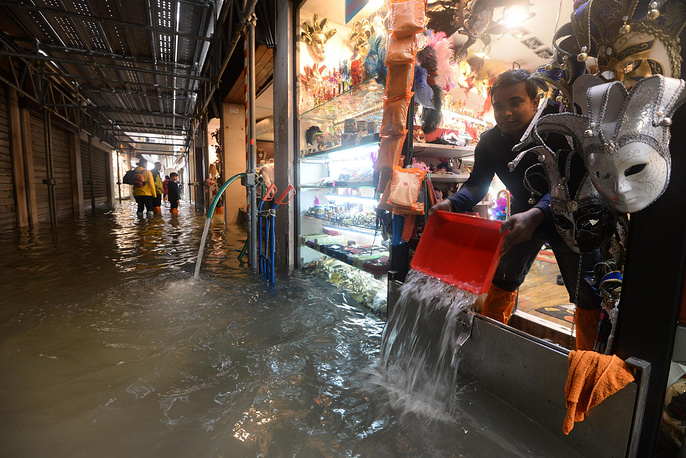 A shopkeeper tries to stop the water that invades the store in Venice