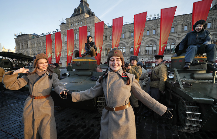 Women dressed in historical uniform dancing near armoured vehicles