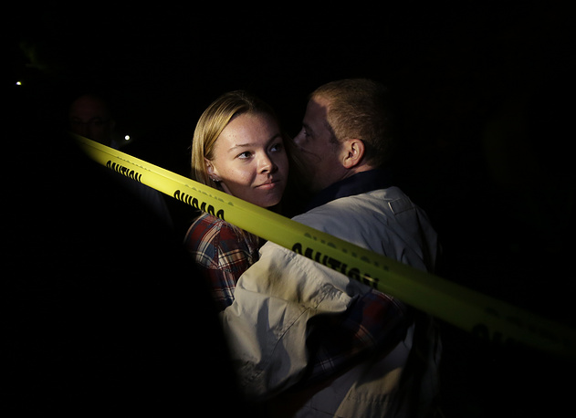 A young woman is hugged by her father after she fled the Borderline Bar and Grill in Thousand Oaks