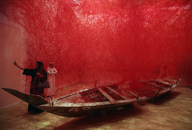 """A woman takes selfie in from of the """"Departure"""" installation by Japanese artist Chiharu Shiota during the launch of Jameel Arts Centre in Dubai, November 11"""
