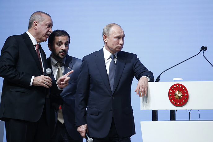 Turkey's President Recep Tayyip Erdogan talks through an interpreter to Russian President Vladimir Putin as they attend an event marking the completion of one of the phases of the Turkish Stream natural gas pipeline, in Istanbul, November 19