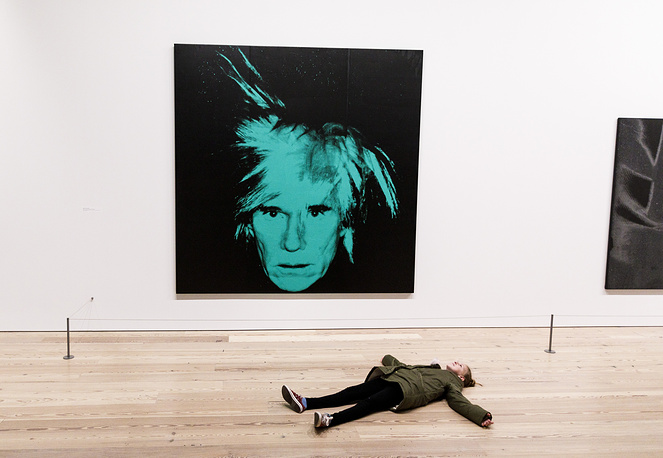 A girl lies on the floor near a self portrait of Andy Warhol at the show 'Andy Warhol - From A to B and Back Again' at the Whitney Museum of American Art in New York, November 20