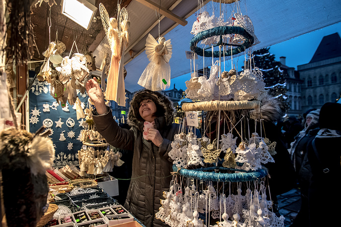 A visitor looks at Christmas decorations at the Christmas market at the Old Town Square in Prague, Czech Republic