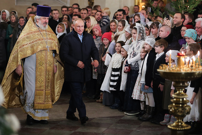The senior priest of Transfiguration Cathedral Nikolai Bryndin and Russia's President Vladimir Putin are seen during a Christmas liturgy at the Transfiguration Cathedral, Saint Petersburg, January 6