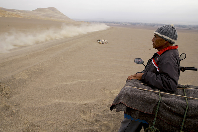 A man leans against his motorbike as he watches competitors pass during the stage eight of the Dakar Rally between San Juan de Marcona and Pisco, Peru
