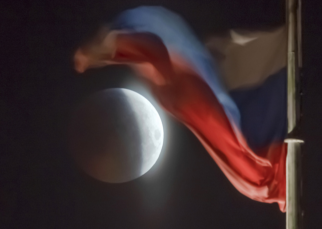 A lunar eclipse is seen behind a Russian national flag in St. Petersburg